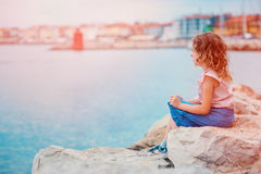 Happy child girl on seaside on summer vacation in Piran, Slovenia, with city view on background Royalty Free Stock Photography