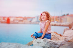 Happy child girl on seaside on summer vacation in Piran, Slovenia, with city view on background Royalty Free Stock Images