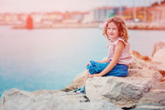 Happy child girl on seaside on summer vacation in Piran, Slovenia, with city view on background Royalty Free Stock Photo