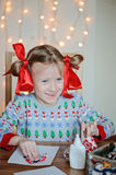 Happy child girl in seasonal sweater making Christmas post cards Stock Image