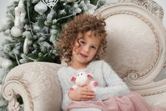 Happy child girl with sheep toy and Christmas tree Royalty Free Stock Image