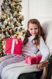 Happy child girl sitting on armchair covered with a blanket against decorated christmas fireplace.  Royalty Free Stock Images