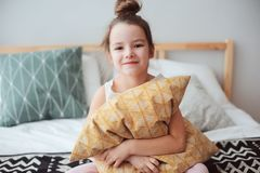 Happy child girl sitting on bed and hugs pillow, waking up in early morning or going to sleep. Kid in comfortable room enjoying weekend royalty free stock photography
