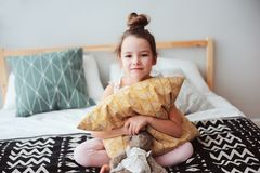 Happy child girl sitting on bed and hugs pillow, waking up in early morning or going to sleep. Kid in comfortable room enjoying weekend stock image