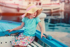 Happy child girl sitting in old boat on summer vacation in Piran, Slovenia Stock Images