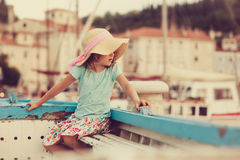 Happy child girl sitting in old boat on summer vacation in Piran, Slovenia Stock Photo