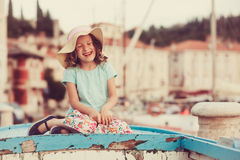 Happy child girl sitting in old boat on summer vacation in Piran, Slovenia Stock Photography