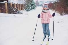 Happy child girl skiing in winter snowy forest, spending holidays outdoor. stock image