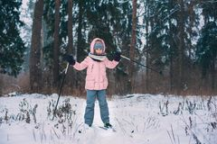 Happy child girl skiing in winter snowy forest, spending holidays outdoor. royalty free stock images