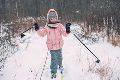 Happy child girl skiing in winter snowy forest, spending holidays outdoor. Active winter sports stock photos