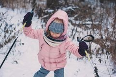 Happy child girl skiing in winter snowy forest, spending holidays outdoor. royalty free stock photography