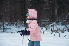 Happy child girl skiing in winter snowy forest, spending holidays outdoor. stock photo