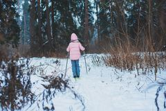 Happy child girl skiing in winter snowy forest, spending holidays outdoor. stock images