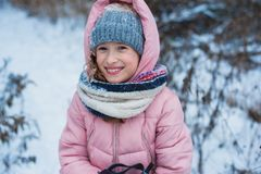 Happy child girl skiing in winter snowy forest, spending holidays outdoor. stock photography