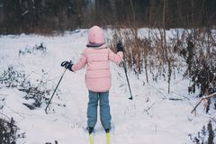 Happy child girl skiing in winter snowy forest, spending holidays outdoor. royalty free stock photos