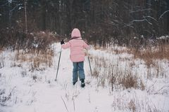 Happy child girl skiing in winter snowy forest, spending holidays outdoor. stock photos