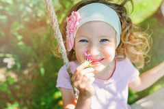 Happy child girl smells flower on swing in summer Royalty Free Stock Image