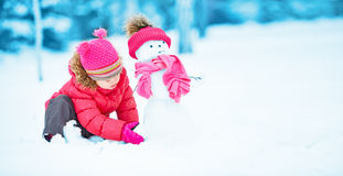 Happy child girl with a snowman on a winter walk Stock Photo
