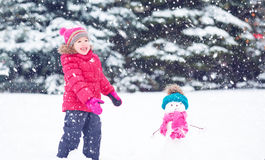 Happy child girl with a snowman on a winter walk Royalty Free Stock Photos