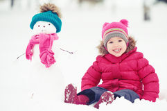 Happy child girl with a snowman on a winter walk Stock Photos