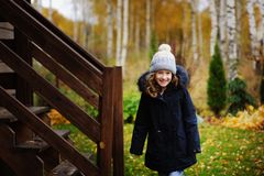 happy child girl standing by wooden house stairs in late autumn garden Stock Photo