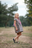 Happy child girl stands on walk in park. Stock Photo