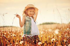Happy child girl in straw playing with blow balls on summer field Royalty Free Stock Image