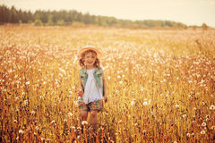 Happy child girl in straw playing with blow balls on summer field Stock Photo