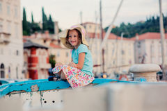 Happy child girl in straw on summer vacation in Piran, Slovenia, sitting on boat with city view on background Royalty Free Stock Image
