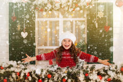 Happy child girl stretches her hand to catch falling snowflakes. Stock Photo