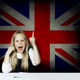 Happy child girl student pointing up and having fun against the UK flag background. Learn English language concept.  royalty free stock images