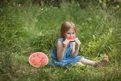 Cute girl eating watermelon in the summer outdoor. Healthy snack for children stock image
