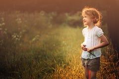Happy child girl on summer sunset field Royalty Free Stock Photos