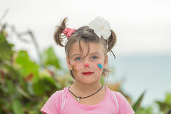 Happy child girl with surprised reaction on her painted face standing near the beach against the ocean and tropical garden backgro Stock Photography