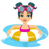 Happy child girl swimming in pool on inflatable ring Stock Photo