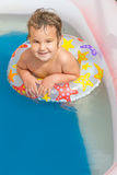 Happy child girl swimming in pool with swimming ring Royalty Free Stock Photos