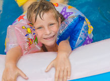 Happy child girl swimming in pool with swimming ring Royalty Free Stock Images