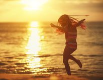 Happy child girl in swimsuit with flying hair dancing on  beach at sunset royalty free stock image