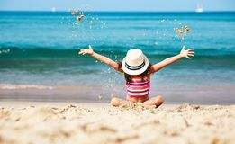Happy child girl with swimsuit and hat on beach at sunset royalty free stock images