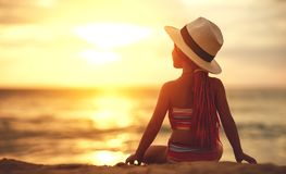 Happy child girl in swimsuit and hat sitting on beach at sunset stock photo