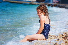 Happy child girl in swimsuit relaxing on the beach and playing with water. Summer vacation at sea. Stock Photo