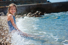 Happy child girl in swimsuit relaxing on the beach and playing with water. Summer vacation at sea. Stock Image