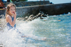 Happy child girl in swimsuit relaxing on the beach and playing with water. Summer vacation at sea. Stock Photography