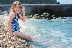 Happy child girl in swimsuit relaxing on the beach and playing with water. Summer vacation at sea. Stock Images