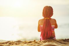 Happy child girl in swimsuit sitting on beach at sunset stock images