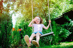 Happy child girl on swing in sunny summer garden Royalty Free Stock Photos
