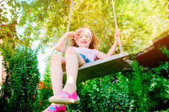 Happy child girl on swing in sunny summer garden Stock Photography