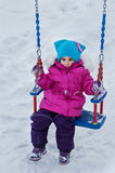 Happy child girl on swing in sunset winter. Little kid playing on a winter walk in nature Stock Photography