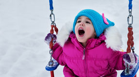 Happy child girl on swing in sunset winter. Little kid playing on a winter walk in nature Royalty Free Stock Images