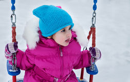 Happy child girl on swing in sunset winter. Little kid playing on a winter walk in nature Royalty Free Stock Photography